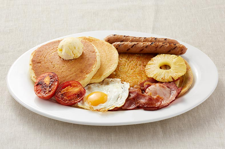 Pancakes, hashbrown, eggs, sausages, tomatoes